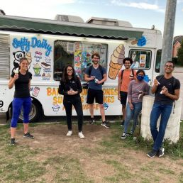 Prof Christina Guzzo and five lab members by an ice cream truck, smiling as they enjoy their ice cream