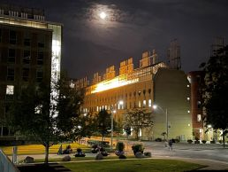 Yellow lights glow from greenhouses on top of the Earth Sciences Building at night, with the moon glowing above and Huron Street below